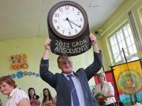 Daudzeses skolas direktors Valdis Puida ar absolventu dāvāto laika rādi