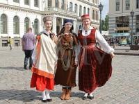Rīgas viesi var fotogrāfēties ar meitenēm latviešu tautas tērpos